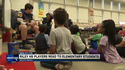 Football players from Riley High School participate in reading session at Monroe Elementary