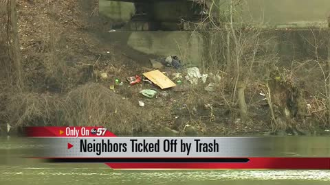 Neighbors upset over trash pile under a walking bridge along St. Joseph River