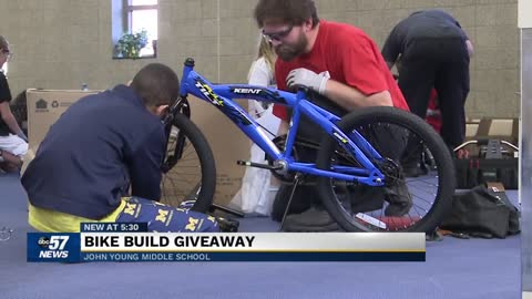 Local company's employees help John Young Middle School students build bikes