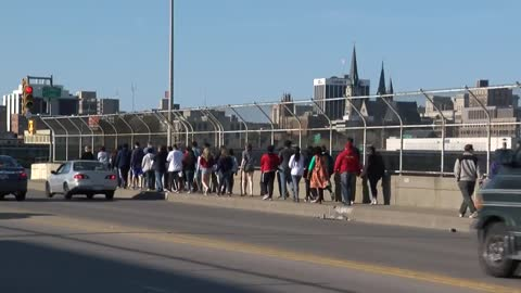 Milwaukee students walk along 16th Street Viaduct with a message