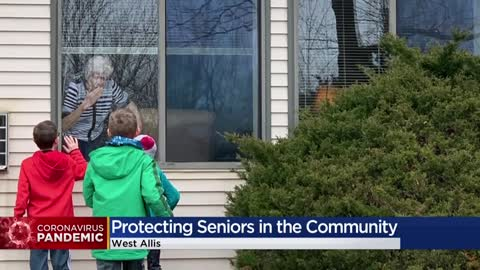 Families affected by senior facility lockdowns communicate through windows, over the phone